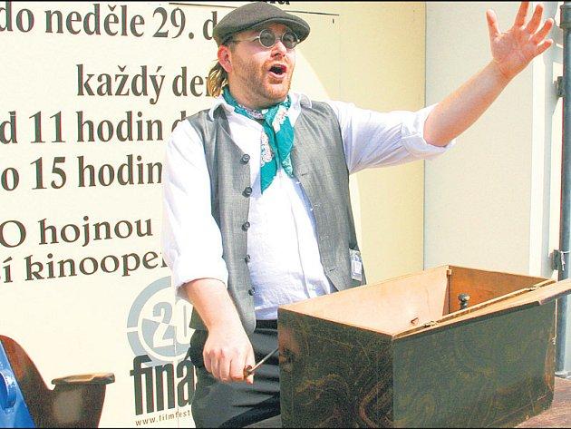 František Šimánek vyhrává na flašinet a zve návštěvníky do rodinného bijáku na originály starých filmů.