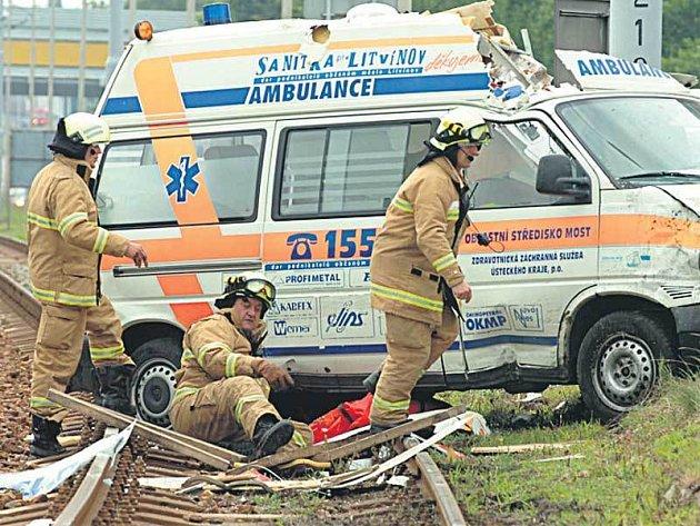 Hasiči vyprošťují záchranku, která ležela napříč kolejištěm v Záluží u Mostu.