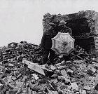 Vojáci zkoumají nalezený deštník. Mezi ruinami působí značně nepatřičně.
