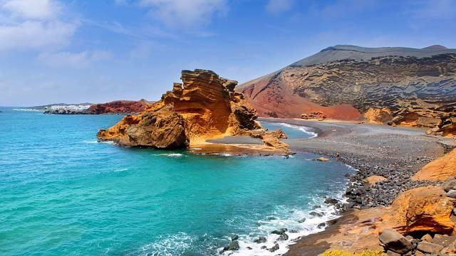 Průzračná voda Atlantického oceánu a rudé krajina jasně vystihují drsné Lanzarote, nejsevernější z Kanárských ostrovů.