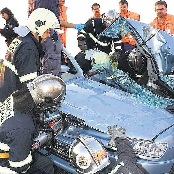 Záchranáři vytahují řidiče z vraku svého auta.