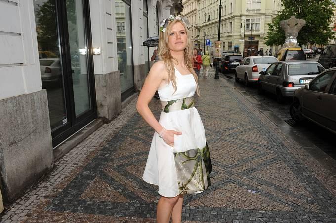 Veslušivých bílých letních šatičkách opouštěla butik Beaty Rajské.