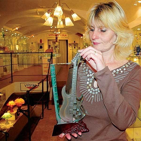 Manželka majitele sklářské dílny paní Frajtová představuje kytaru, kterou předali Petru Kolářovi.