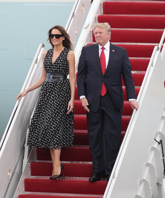 First Lady Melania Trump in a sleeveless black and white print dress with an oversized Steve McQueen leather belt and Louboutin shoes arrives on Air Force One in West Palm Beach, Florida.