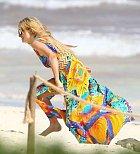 Miliardářská dědička pobíhala po pláži v barevných šatech.