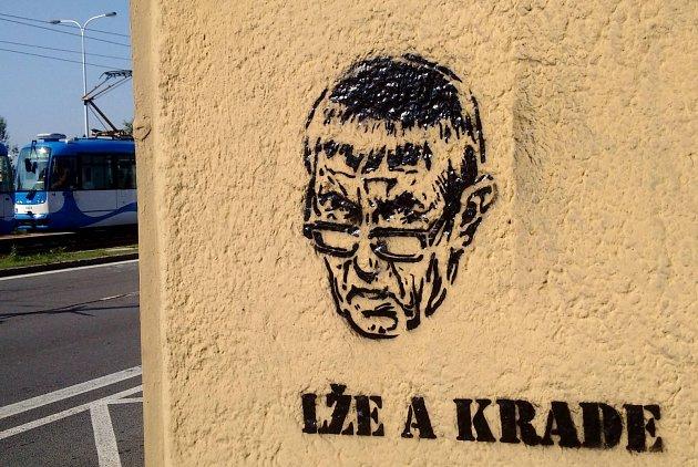 Lže a krade! To stojí uportrétů současného předsedy české vlády, které se objevují nastříkané pravděpodobně za pomocí šablony na zastávkách ostravské městské hromadné dopravy.