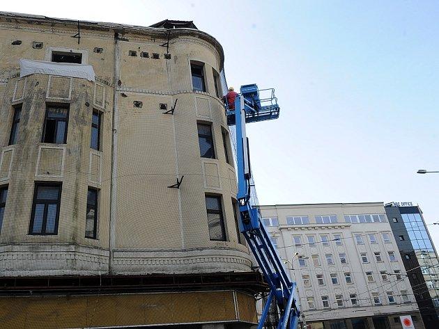 """Polorozpadlý bývalý Módní dům Ostravica Textilia v Nádražní ulici dále chátrá. V úterý ho dělníci """"zabalili"""" do speciální sítě, aby neohrožoval kolemjdoucí."""