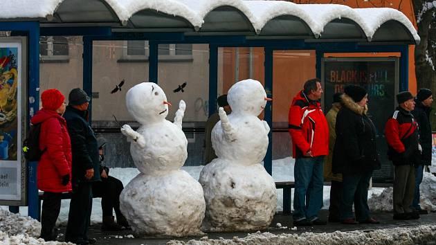 Sněhuláci na zastávce autobusů u vozovny v Porubě.