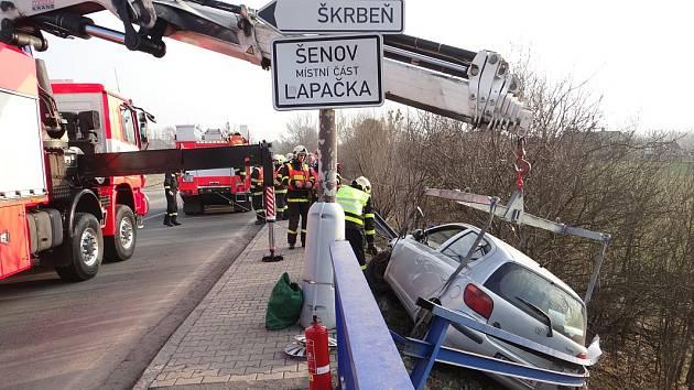 Páteční nehoda vozu Toyota Yaris, který skončil vedle silnice - ve srázu jej drželo pouze pokroucené zábradlí.