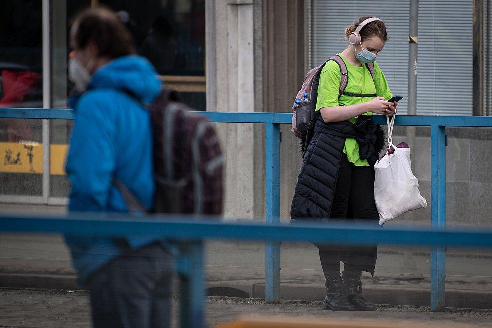 Žena s rouškou na zastávce MHD, 25. února 2021 v Ostravě. Kvůli koronavirové epidemii začala platit povinnost na frekventovaných místech nosit respirátor nebo dvě jednorázové zdravotnické roušky přes sebe.