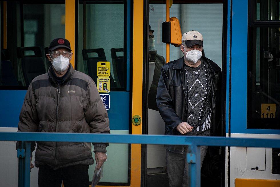 Lidé vystupují s respirátorem z MHD, 25. února 2021 v Ostravě. Kvůli koronavirové epidemii začala platit povinnost na frekventovaných místech nosit respirátor nebo dvě jednorázové zdravotnické roušky přes sebe.