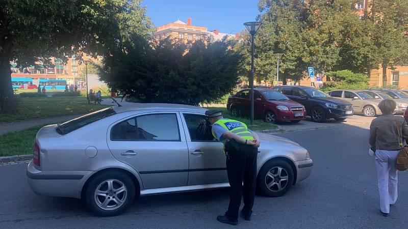 Vjezd do Alšovy ulice hlídá policie a nepouští tam žádná auta. Informace o evakuaci hlásí policisté z amplionu.