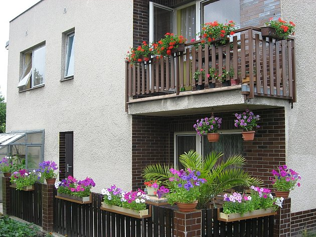 Rozkvetlý balkon, okno, zahrada