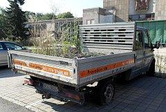 Odstavený pickup s porostem na korbě před kulturním domem Poklad v Ostravě-Porubě.