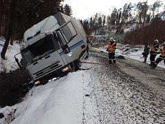 Nákladní automobil Iveco skončil nebezpečně nakloněný nad potokem.