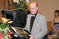 Petr Ciba, dirigent  dechového orchestru Harmonie ze Šternberku přebírá na ostravské soutěži dechových hudeb cenu pro vítěze - mistrovský lesní roh