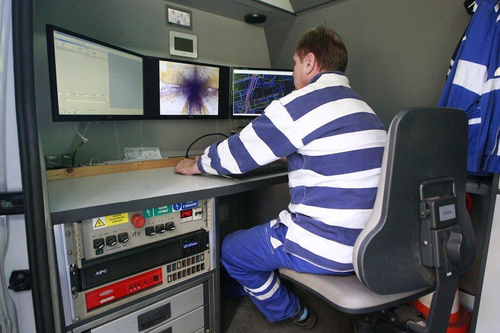 Pracovníci OVAK spouštějí do podzemí speciální kameru. Ta je umístěna na malém vozíku. Jejich kolegové ve voze pak sledují na monitoru, v jakém stavu potrubí je.