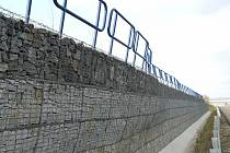 Stěna z ocelových košů plněných kamením, neboli gabionů, má funkci opěrnou a ochrannou. U Krásného Pole je ale poškozená a na Prodloužené Rudné přidělává potíže.