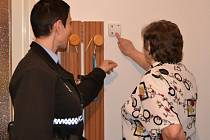 Městská policistka ukazuje seniorce z Mariánských Hor, jak se spouští tlačítko nouze.
