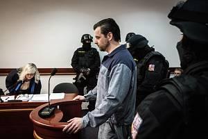 Petr Kramný v jednací síni v doprovodu ozbrojené vězeňské eskorty.
