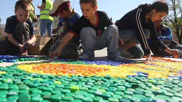 Plastová víčka od lahví se stala stavebním materiálem pro obrazce, které děti ve středu skládaly na náměstí Svatopluka Čecha v Ostravě-Přívoze v rámci oslav Dne Země.