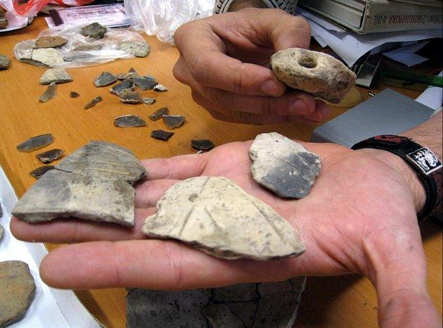 Nalezené kousky pazourků a střepy.