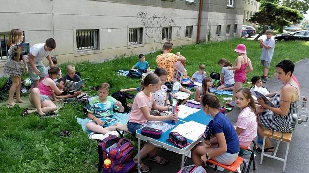 Vlastivěda ve IV. A na trávníku a chodníku na západní stinné straně porubské ZŠ Komenského.