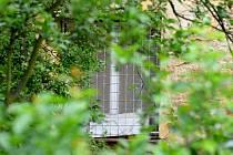 Za tímto oknem s mřížemi v zadní části domu se podle sousedů Herič ukrýval. Policisté se do místnosti snažili dostat dveřmi z chodby. Byly zajištěné velkým množstvím zámků, se kterými si neporadilo ani beranidlo. Pomohli hasiči se speciální technikou.