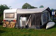 Letní byt kamarádů z Ostravy, kteří si plní svůj sen. Komfort v přístřešku u karavanu, takřka jako doma.