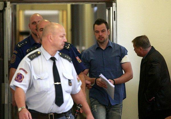 Petr Kramný vdoprovodu eskorty na chodbě ostravského soudu.