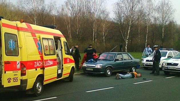 Záchranáři za osobním vozidlem poskytují první pomoc postřelené spolujezdkyni. Opilý řidič leží spoutaný zemi