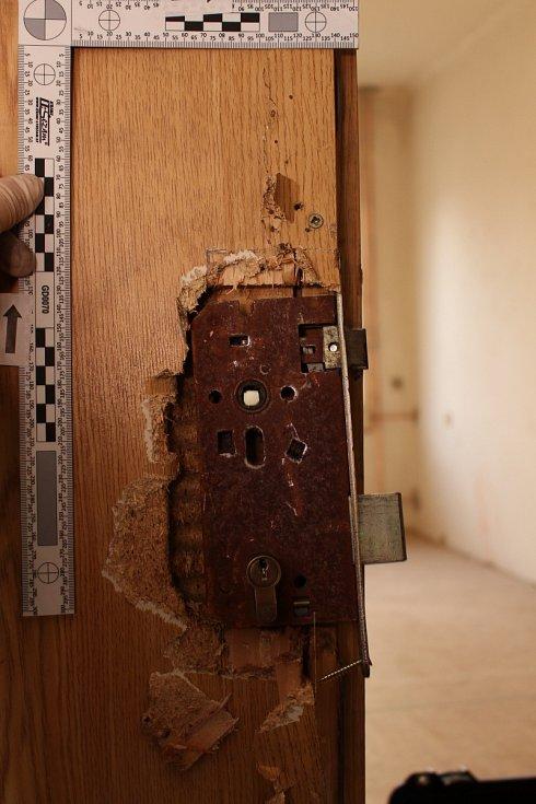 Snímky z místa činu. Poškozené dveře.