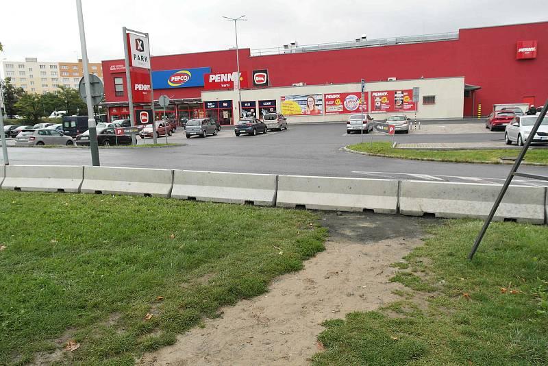Plot bude stát u silnice mezi paneláky a nákupním střediskem.