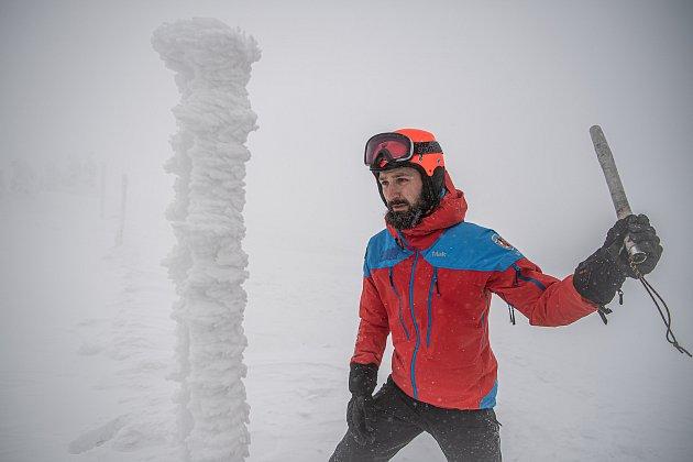 Dobrovolník horské služby Michal Vávra oklepává tyčové značení, 30.ledna 2021na Pradědu.
