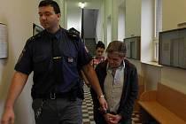 Vězeňská eskorta přivádí Václava Bojdu a Nikol Buzášovou. Poslední obžalovaný – Vlastimil Kocúr – je souzen na svobodě.
