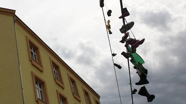 Na drátech elektrického vedení u zastávky Stodolní v centru Ostravy visí několik párů bot včetně zelených plaveckých ploutví.