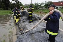 Hasiči v koblovském Žabníku znovu stavějí provizorní protipovodňovou hráz.