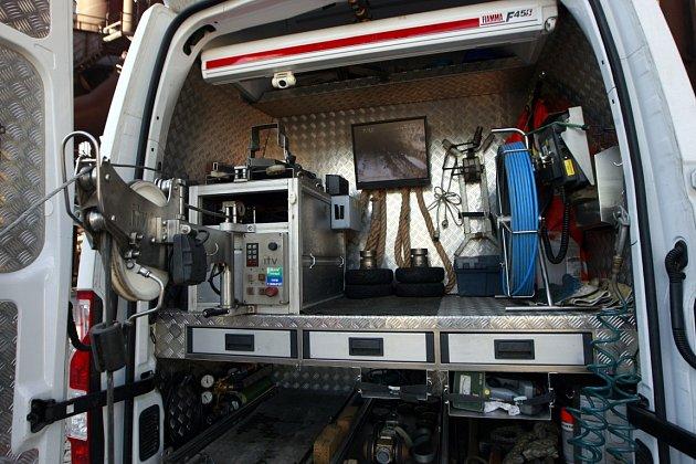 Pracovníci OVAK spouštějí do podzemí speciální kameru. Ta je umístěna na malém vozíku. Jejich kolegové ve voze pak sledují na monitoru, vjakém stavu potrubí je.