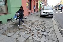 Aby se mohla maminka s kočárkem dostat přes rozbitý úsek chodníku, musí kočárek přenést.