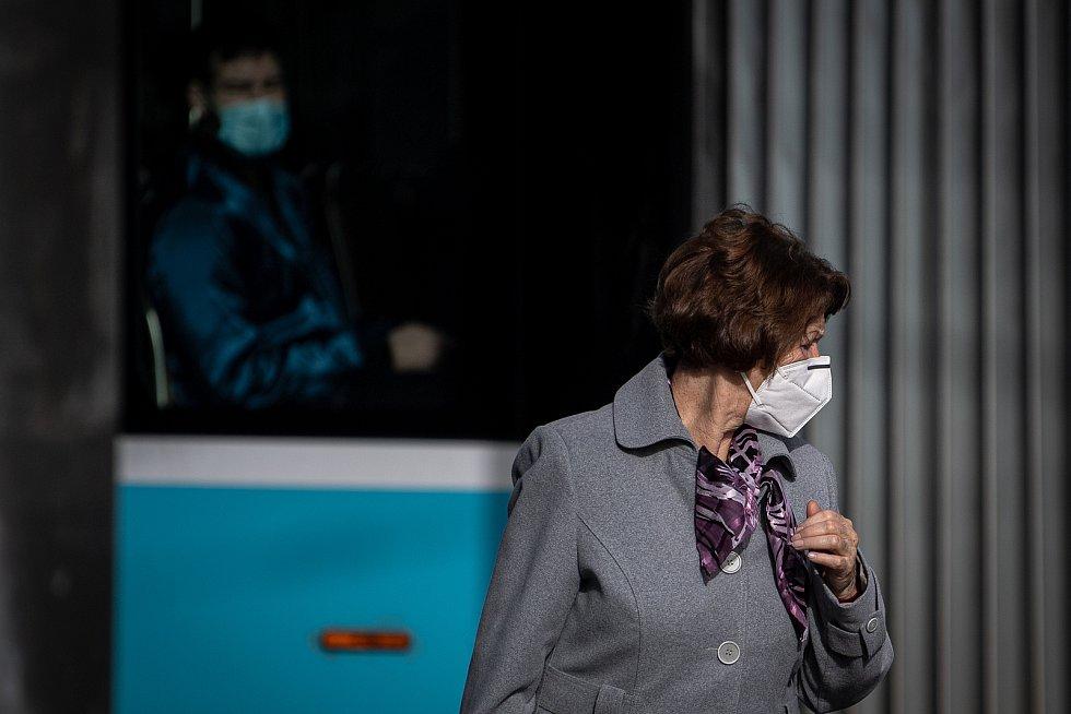 Žena s respirátorem na zastávce MHD, 25. února 2021 v Ostravě. Kvůli koronavirové epidemii začala platit povinnost na frekventovaných místech nosit respirátor nebo dvě jednorázové zdravotnické roušky přes sebe.