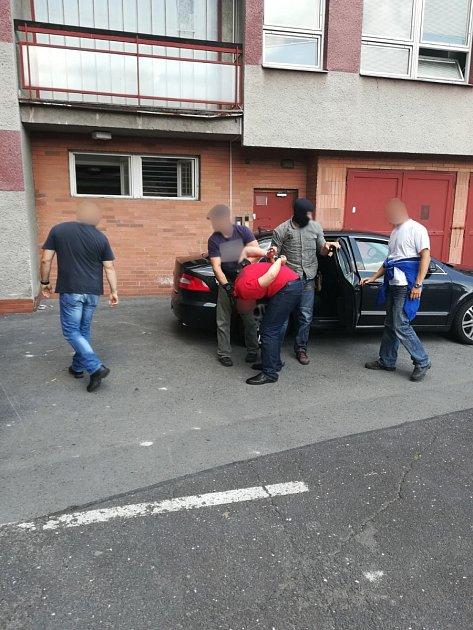 Policisté předvádějí zadrženého mladíka na služebnu.