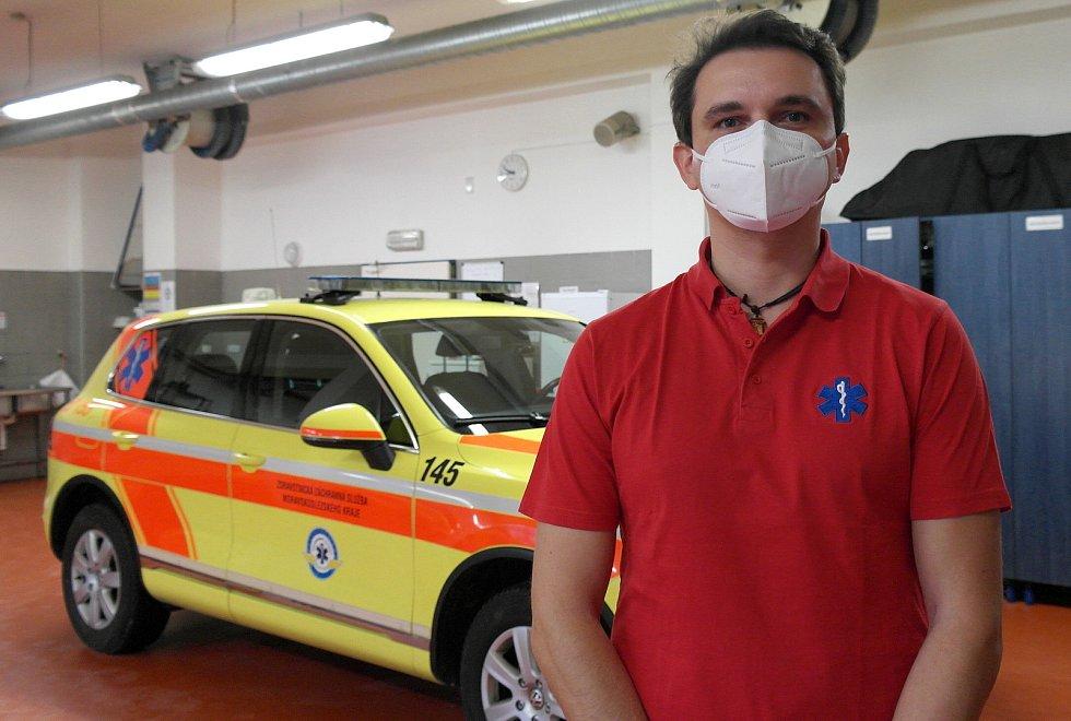 """Vrchní záchranář ostravského územního odboru Adam Hružík v garáži sanitek u SUV """"rande""""."""