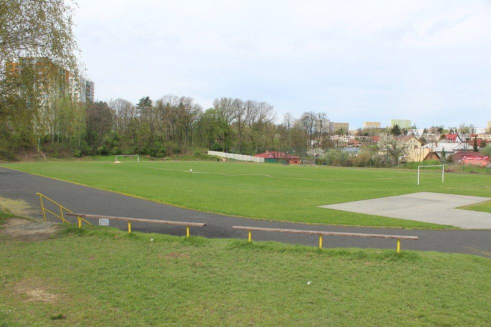 Sportovní areál v Pustkovci s fotbalovým hřištěm a atletickým oválem.