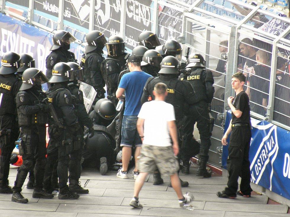 3. Zraněného fanouška policisté vynášejí ven a pokládají na atletickou plochu.