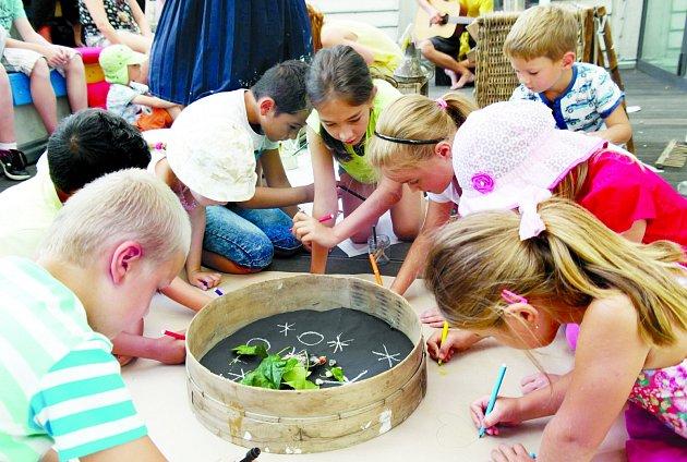 Děti se zdiváků stávají iúčinkujícími, zdobí hrobeček pro kosa a kreslí mu něco na památku.