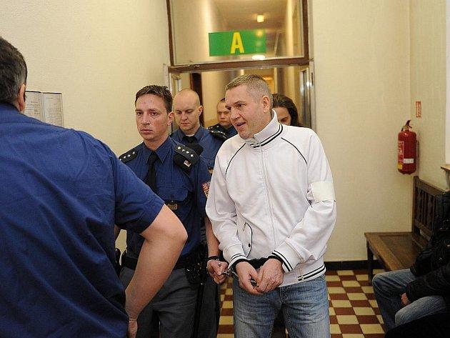 Pavel Ošlejšek (v bílém) v doprovodu vězeňské eskorty.