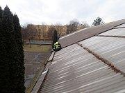 Zásah hasičů na větrem poškozené střeše sportovní haly v ostravské Gajdošově ulici.