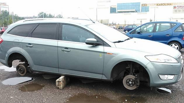 Ford Mondeo stál na betonových špalcích bez kol na lidovém parkovišti za nákupní střediskem Nová Karolina v centru Ostravy.