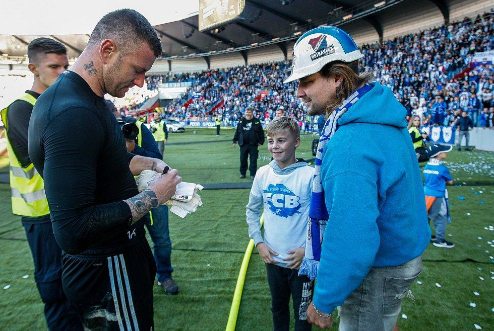 Jan Laštůvka podepisuje rukavice fanouškovi baníku