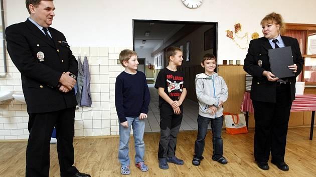 Poctiví školáci (zleva Matyáš Haladěj, Jan Harabiš a Pavel Chovanec) v úterý z rukou zástupců městské policie převzali ocenění a drobné dárky.